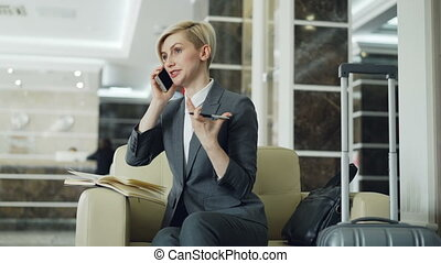 blonde cheerful businesswoman sitting in armchair in hotel lobby talking mobile phone and gesturing hand holding pen . Business, travel and people concept