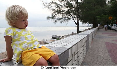 blonde child ate biscuits naughty holding hands at seafront