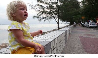 blonde child ate biscuits naughty holding hands at seafront...