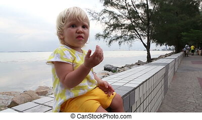 blonde child holds out hand for food at seafront