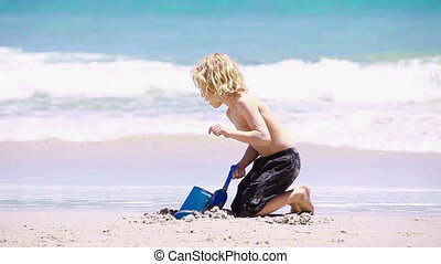 Blonde child playing with a shovel on the beach