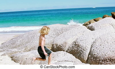 Blonde child playing with a wooden stick on the beach