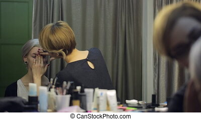 Blonde chinese woman carefully applies makeup on face of...