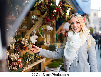 Blonde choosing christmas decorations