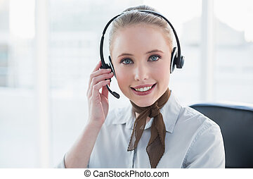 Blonde content businesswoman wearing a headset in bright ...
