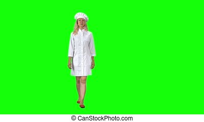 Blonde cook chef in white uniform and hat going and looking straight into the camera against a green screen. . Slender girl with bright eyes focused