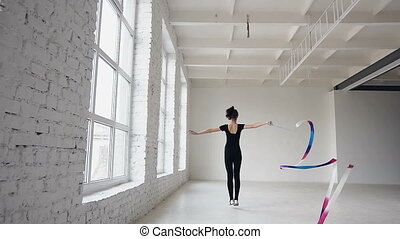 Blonde cute girl dance rhythmic gymnastics, modern with colored ribbon in black bodysuit in front of the windows. Attractive female gymnast jumping with ribbon in the gymnastics school or ballet school