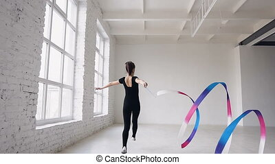 Blonde cute girl rhythmic gymnastics, modern with colored ribbon in black bodysuit in indoors at white bacground . Attractive gymnast girl jumping with ribbon in the gymnastics school or ballet school near big windows