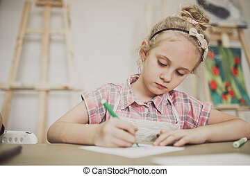 Blonde cute seven-year-old girl, draws at the table in the creative studio