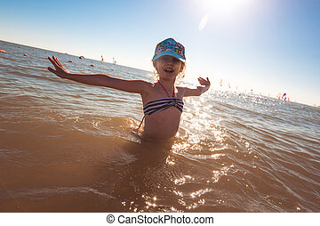 Blonde cute seven-year-old girl having fun and having a good time at the sea during the holidays