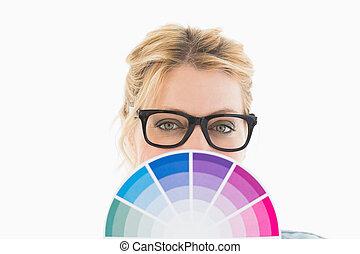 Blonde designer holding colour wheel