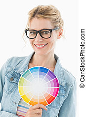 Blonde designer holding colour wheel smiling at camera