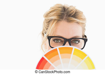 Blonde designer wearing glasses holding colour wheel