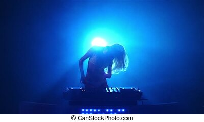 Blonde DJ plays track and erotically dancing. Slow motion