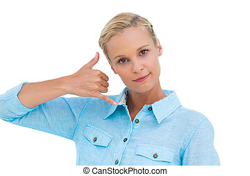 Blonde doing a symbol of phone with her hand and looking at...