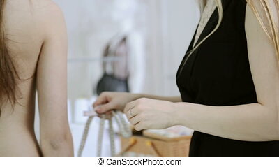 Blonde dressmaker takes measurements woman for sewing. seamstress in black dress with long white straight hair holding meter, measures nacked client in waist writes down results in workbook indoors. Blond female standing back to camera, waiting for dress clothes in studio. Women work in field of ...