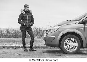 Blonde driver woman standing next to car
