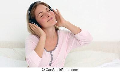 Blonde enjoying music in bedroom