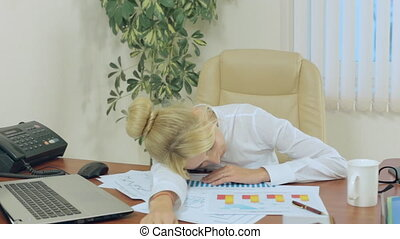 Blonde fell asleep on the table and the papers in office
