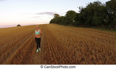 blonde fitness woman running on the field
