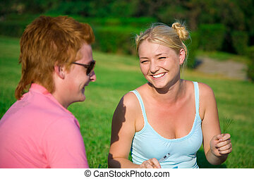 blonde funny girl with red head cute boy in the park