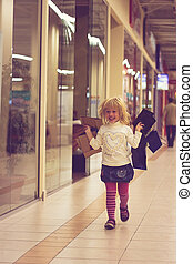 Blonde girl 3 years old running with shopping