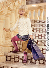 Blonde girl 3 years old standing with shopping