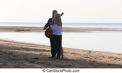 blonde girl and bearded guitarist walk towards sea