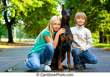 blonde girl and boy hugs beloved dog or doberman in summer park