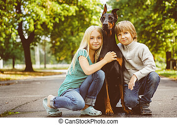 blonde girl and boy hugs beloved dog or doberman in summer park. Warm toned image