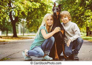 blonde girl and boy hugs beloved dog or doberman in summer park. Warm toned image