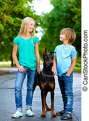 blonde girl and boy posing with beloved dog or doberman in summer park