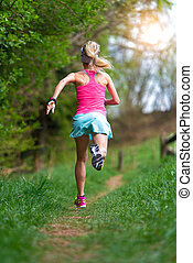 Blonde girl athlete running in a trail into the woods