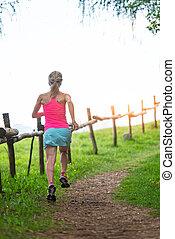 Blonde girl athlete runs a mountain path in the green grass