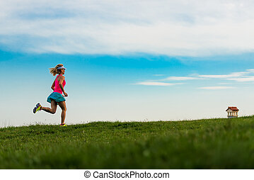 Blonde girl athlete runs in a green meadow in the hills
