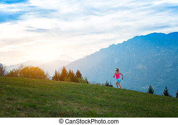 Blonde girl athlete runs in the mountains