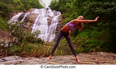 Blonde Girl Bends Body in Yoga Pose at Waterfall
