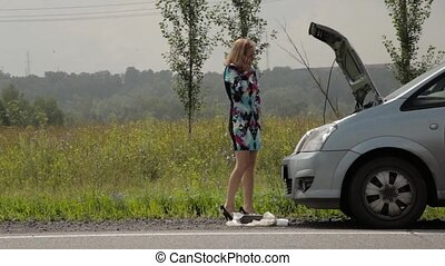 blonde girl calling cellphone in a panic near her broken car with open hood on a country road