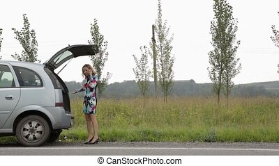 blonde girl calling cellphone in a panic near her broken car with open trunk on a country road