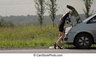 blonde girl calling cellphone in a panic near her broken car...