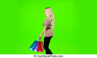 Blonde girl carries a lot of different color packages. Green screen. Side view
