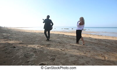 blonde girl chases leaving  bearded guitarist on beach at sunrise