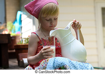 blonde girl drinking milk outside