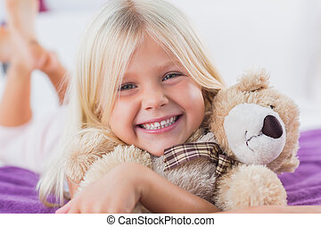 Blonde girl embracing her teddy bear