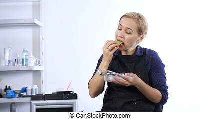 Blonde girl have a lunch at workplace, fast junk food....