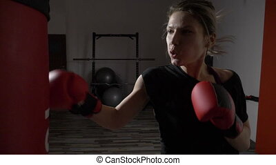 Blonde girl hitting the punching bag nervously in the gym after breaking up with her boyfriend in slow motion
