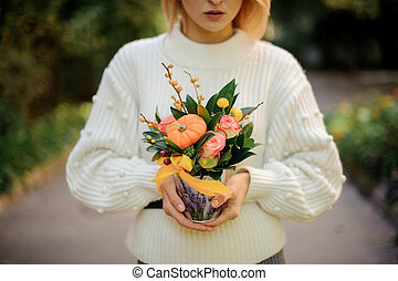Blonde girl holding a box of roses decorated with pumpkin