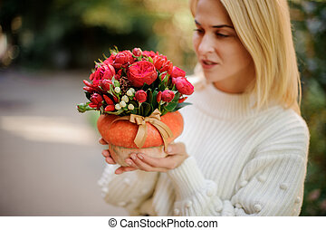 Blonde girl holding a pumpkin decorated with red flowers