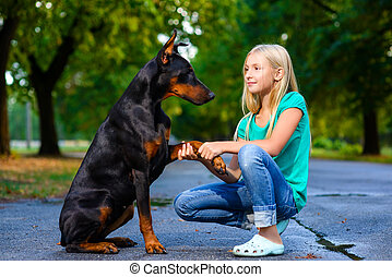 blonde girl holding dog or doberman paw in summer park