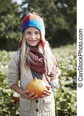 Blonde girl holding pumpkin in hands